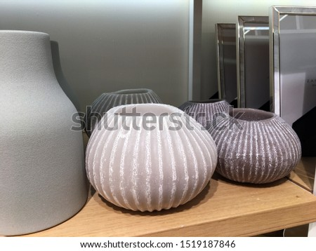 Vases of various shapes on a shelf in a store. Gray minimalist tall vase. Rippled ceramic vases. Decor and tableware shop. Various types of colorful vases set on shelves