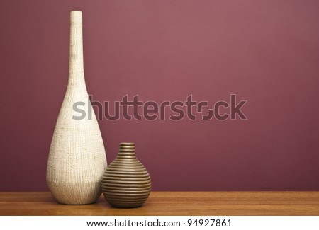 Vases on a table in front of a burgundy wall