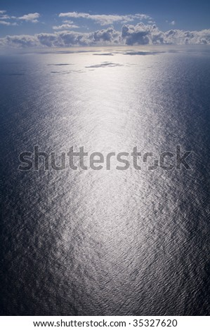 Vast aerial of the ocean emphasizing the extreme glare at sea with clouds in the background