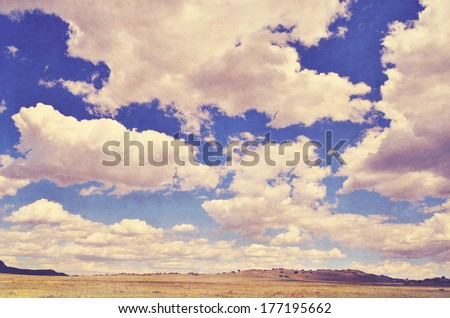 Vast arid landscape and huge sky with clouds, vintage retro look on textured background