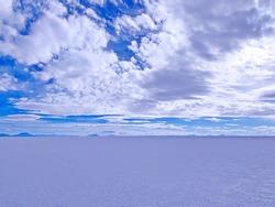 Vast desert cloudscape in heaven sky in first evening blue twilight, endless area salt flat Salar de Uyuni, infinity landscape, unique terrain.