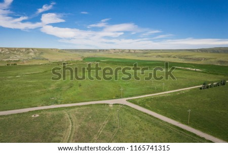 Vast green farm fields and ranchlands in the wide American midwest.
