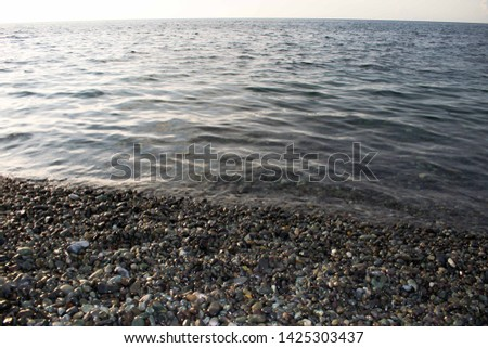 Vast ocean with smooth cobblestones or smooth pebbles. Clear water beach