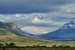 vast open landscape in Patagonia with dramatic sky and a rainbow over a valley, snow covered mountains of the Andes in the background