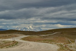 vast open landscape in Patagonia with snow covered mountains of the Andes in the background and a gravel road leading through the frame