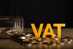 Vat Concept.Word vat put on coins and glass bottles with coins inside on black background.