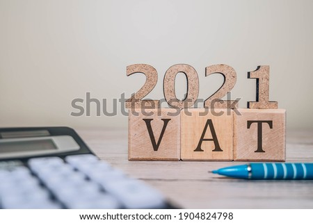 VAT 2021 on wooden cubes, calculator and a pen on a wooden table. VAT 2021 - phrase from wooden blocks with letters, VAT 2021 concept