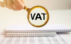 VAT text, Value Added Tax, inscription through magnifying glass over office table.