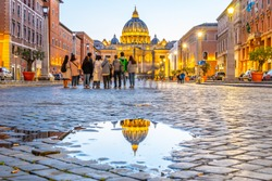 Vatican City by night. Illuminated dome of St Peters Basilica and St Peters Square. Group of tourists on Via della Conciliazione. Rome, Italy.