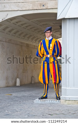 VATICAN CITY, ITALY - MARCH 23: A Papal Swiss Guard stands guard at the entrance of Saint Peter's Basilica on March 23, 2012. Swiss Guards in their traditional uniform.