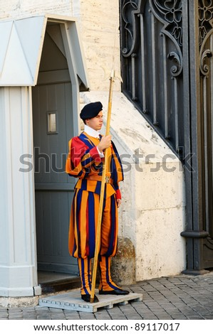 VATICAN CITY, ITALY - SEPTEMBER 15: A Papal Swiss Guard stands guard at the entrance of Saint Peter's Basilica on September 15, 2011. Swiss Guards in their traditional uniform.