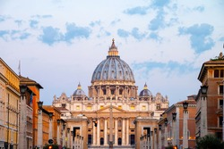 Vatican City. Sunrise over the St. Peters Basilica in Vatican City. Morning at the most famous landmark, empty of people street, cloudy sky.