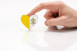 Vatican flag. Love and respect Vatican. A man's hand holds a heart in the shape of the Vatican flag on a white glass surface. Respect for Catholics
