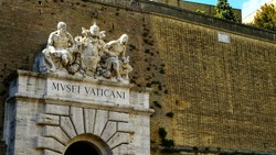 Vatican Museums written in Italian at the external entrance of the museums on the Vatican walls, with a group of marble statues and papal coat of arms, seen from the street