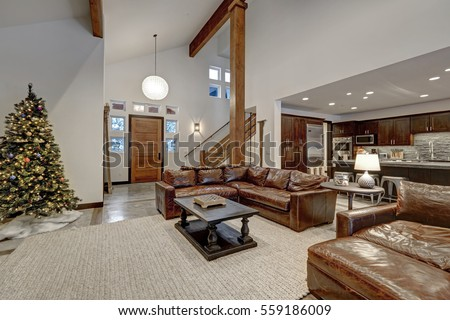Vaulted ceiling living room accented with wood beams over  brown leather sofas. Open floor plan. Northwest, USA #559186009