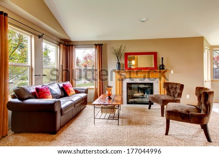 Vaulted ceiling living room with soft carpet floor and cozy fireplace. Furnished with leather couch, antique style chairs and rustic wooden coffee table