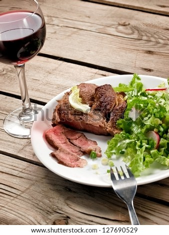 Veal meat with green salad with a red wine glass