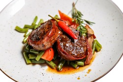 Veal medallions with green beans and chilli pepper on a plate isolated on a white background