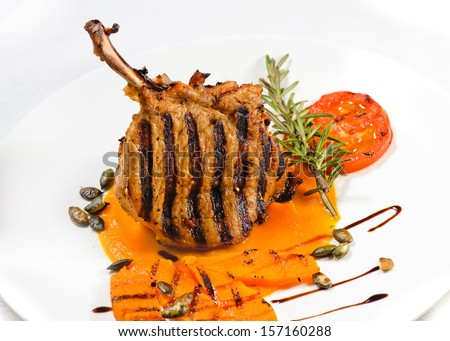 Veal on the bone. Grilled meat ribs on white plate with tomatoes and sauce in pumpkin