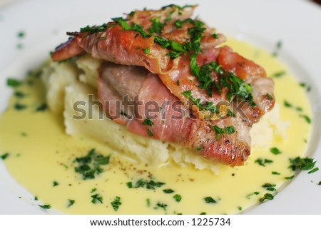 Veal Scallopine wrapped in prosciutto on creamy mash with Beure blanc. Close crop landscape from above.