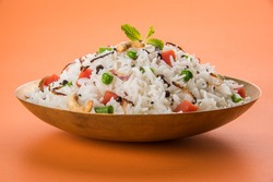 Veg biryani or veg pulav served in a round brass bowl, selective focus