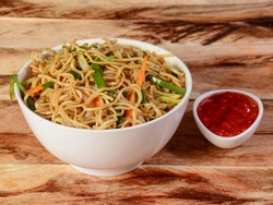 Veg Hakka Noodles a popular oriental dish made with noodles and vegetables, served over a rustic wooden background, selective focus
