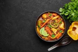 Veg Kolhapuri in black bowl on dark slate table top. Indian vegetable curry dish. Vegetarian asian food and meal. Copy space. Top view