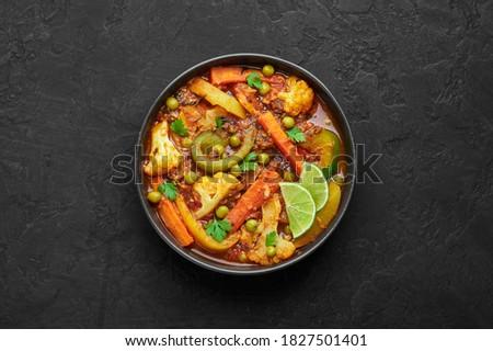 Veg Kolhapuri in black bowl on dark slate table top. Indian vegetable curry dish. Vegetarian asian food and meal. Top view Stock fotó ©