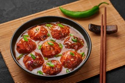 Veg Manchurian Gravy Balls in black bowl in dark slate table top. Vegetarian Manchurian is indian chinese cuisine dish. Asian food and meal