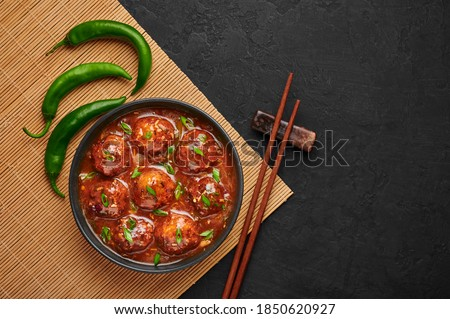 Veg Manchurian Gravy Balls in black bowl in dark slate table top. Vegetarian Manchurian is indian chinese cuisine dish. Asian food and meal. Top view. Copy space Stock fotó ©