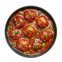 Veg Manchurian Gravy Balls in black bowl isolated on white. Vegetarian Manchurian is indian chinese cuisine dish. Asian food and meal. Top view