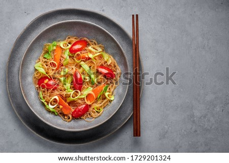 Veg Pad Woon Sen or Thai Glass Noodle Stir-Fry or Pad Thai in bowl on gray concrete backdrop. Vegetarian Pad Woon Sen is a Thai dish of glass bean noodles, tomatoes, carrots, egg, sauces. Thai Food.