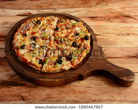 Veg Pizza on wooden pizza board, isolated over a rustic wooden background, selective focus Stock fotó ©