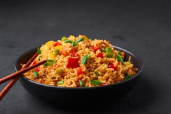 Veg Schezwan Fried Rice in black bowl at dark slate background. Vegetarian Szechuan Rice is indo-chinese cuisine dish with bell peppers, green beans, carrot.