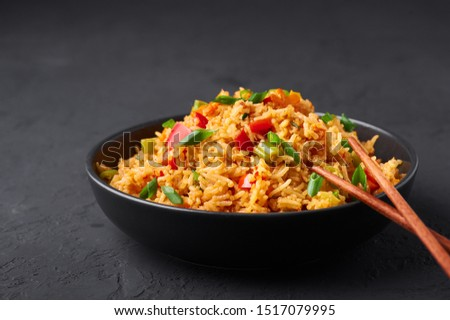 Veg Schezwan Fried Rice in black bowl at dark slate background. Vegetarian Szechuan Rice is indo-chinese cuisine dish with bell peppers, green beans, carrot. Copy space