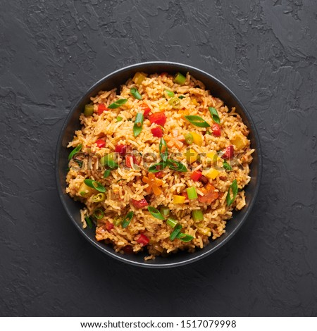 Veg Schezwan Fried Rice in black bowl at dark slate background. Vegetarian Szechuan Rice is indo-chinese cuisine dish with bell peppers, green beans, carrot. Top view