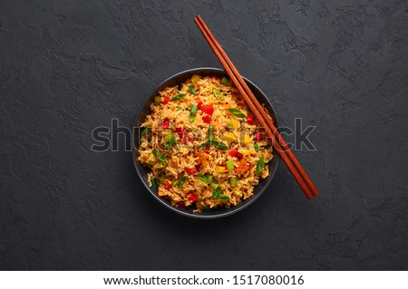 Veg Schezwan Fried Rice in black bowl at dark slate background. Vegetarian Szechuan Rice is indo-chinese cuisine dish with bell peppers, green beans, carrot. Copy space. Top view