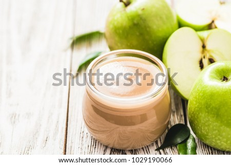 Vegan applesauce in glass jar and green apples on rustic white wooden background. Selective focus, space for text. stock photo