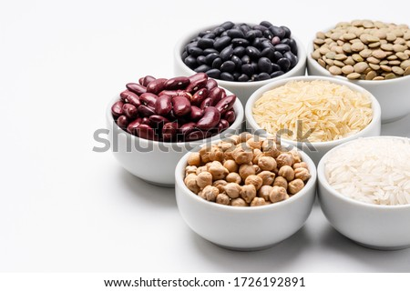 Vegan beans and rice with copyspace. Bowl of basmati rice surrounded by other varieties of grains and legumes, such as: chickpeas, red kidney beans, green lentils, black turtle beans and jasmine rice.