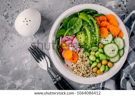 Vegan Buddha bowl salad with spinach, quinoa, chickpeas, avocado, edamame beans, cucumbers, carrots, radish and sesame seeds. Top view