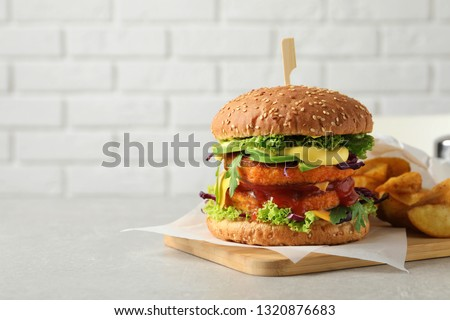 Vegan burger with carrot patties and fried potato served on table against light background. Space for text
