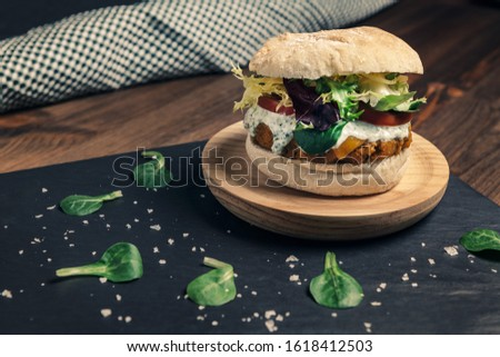 vegan burger with lettuce and tomato on a slate tray with green leaves on a wooden table, vegetarian food and healthy lifestyle concept