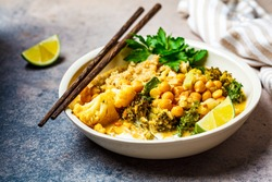 Vegan chickpea curry with cauliflower, broccoli, kale and quinoa. Healthy vegetarian food concept.