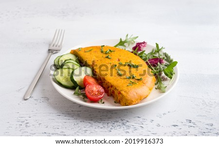 Vegan chickpea omelet with bell peppers served with tomatoes, cucumbers, lettuce and parsley on a light gray textured background. Healthy homemade food Zdjęcia stock ©