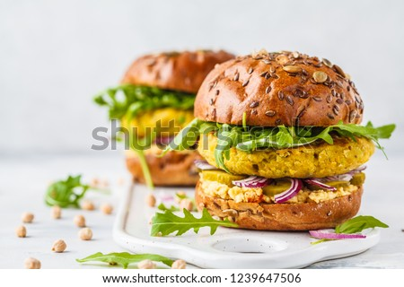 Vegan chickpeas burgers with arugula, pickled cucumbers and hummus. Plant based diet concept.