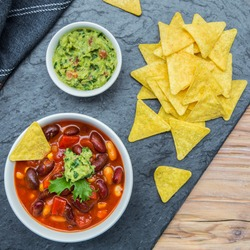 Vegan chili sin carne with beans, carrots, peppers, corn, tomatoes, onions, and garlic served with nachos and guacamole. On a black stone, using natural light.