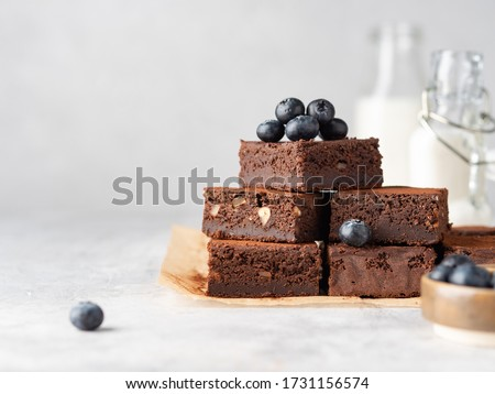 Vegan chocolate brownie with nuts and blueberry. Brownie chewy squares stack with fresh berries and cocoa powder on baking paper. Morning table. Copy space. White background. Photo stock ©