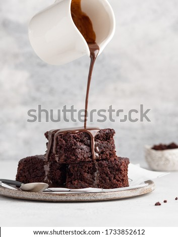 Vegan chocolate brownies made of beetroot puree, dark chocolate, cocoa powder, sugar and coconut cream. Stack of brownie pieces on ceramic plate with pouring melted chocolate sauce. Close up view.