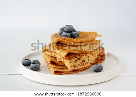 Vegan crepes made from chickpea flour, al purpose gluten free flour and oat milk, with frozen blueberries on a white wooden table Foto stock ©