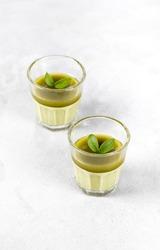 Vegan dessert Panna Cotta green matcha tea in a glass on a light gray background
